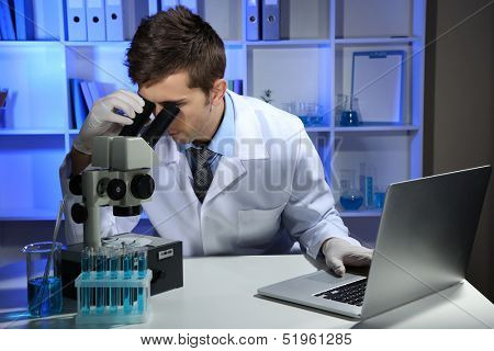 Young laboratory scientist  looking at microscope in lab