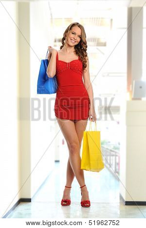 Young Woman wearing a red dress and carrying shopping bags isolated on a white background