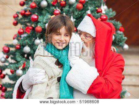 Santa Claus whispering in boy's ear against Christmas tree