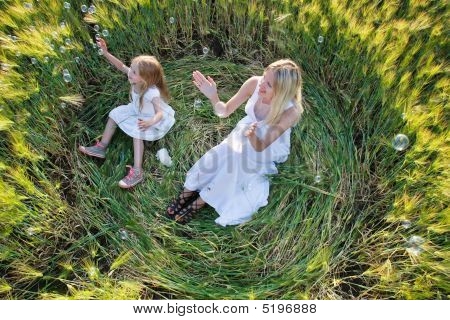 Mother And Daughter Catching Soap Bubbles In Green Field