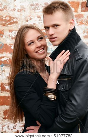 Young enamoured pair at a brick wall