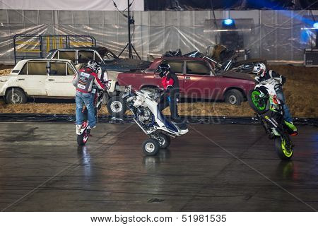 MOSCOW - MAR 23: Three stuntmen rides on the rear wheel of bikes on Show Monster Mania in Olimpiyskiy in March 23, 2013 in Moscow, Russia.