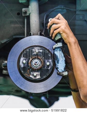 Hands Of A Mechanic Install Brake Lining Onto A Car Disc Brake
