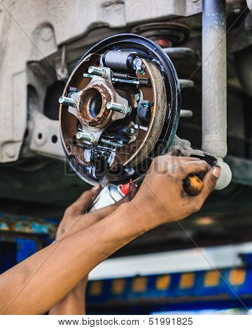 Hands Of A Mechanic Adjusting A Car Drum Brake