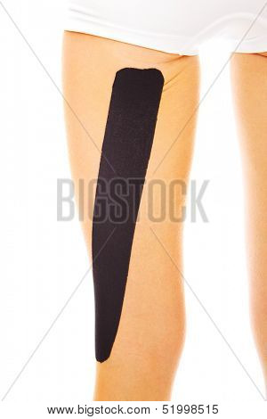 A picture of a special physio tape put on an injured leg muscle over white background