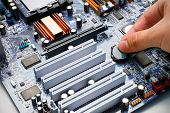 stock photo of cpu  - Hand install battery to PC motherboard - JPG