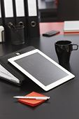 Closeup photo of modern workplace with tablet pc, personal organizer and pen.