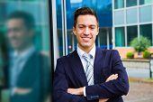 picture of youg  - smiling youg businessman standing in front og building - JPG