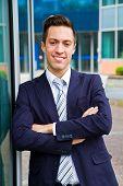 stock photo of youg  - smiling youg businessman standing in front og building - JPG