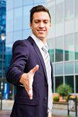 foto of youg  - smiling youg businessman standing in front og building - JPG