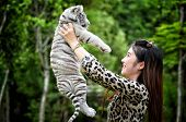 image of white tiger cub  - pretty women hold baby white bengal tiger - JPG