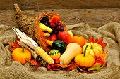 stock photo of cornucopia  - Harvest or Thanksgiving cornucopia filled with vegetables on a burlap and wood background - JPG