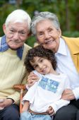 stock photo of grandparent child  - Portrait of a child with his grandparents outdoors - JPG