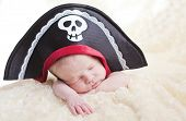 stock photo of pirate girl  - sleeping newborn baby in a pirate hat (soft focus)