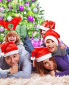 Portrait of happy large family celebrating Christmas holidays at home, lying down near Xmas tree, we