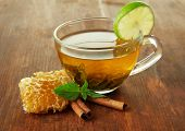 foto of cinnamon  - Transparent cup of green tea with honey and cinnamon on wooden background - JPG