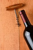 Cabernet Sauvignon bottle and corkscrew on a wooden table. The antique opener and bottle are at an a