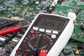 stock photo of multimeter  - Digital multimeter is lying on many circuit boards - JPG