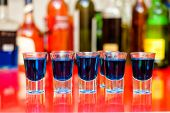 Five Blue Curacao Alcoholic Shots On Bar With Bottles Background