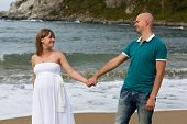 picture of stroll  - Happy pregnant woman and her husband strolling by the sea - JPG