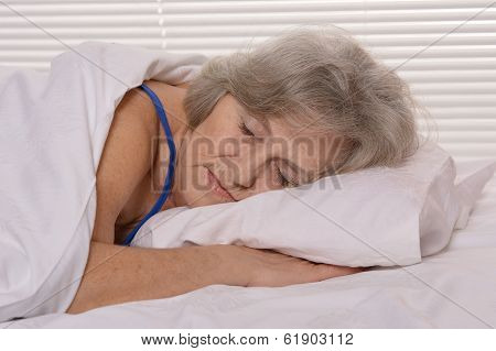 Attractive older woman resting in the bedroom