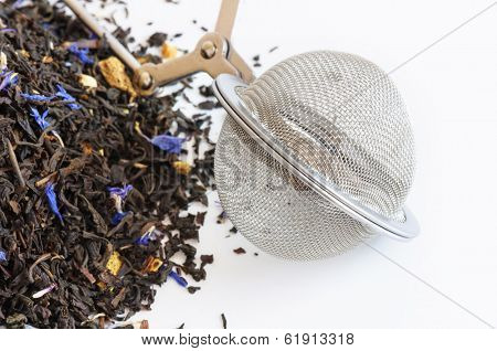 Tea ball infuser and scented tea on white background