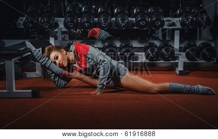 Young attractive woman does splits crossfit stretching in gym club