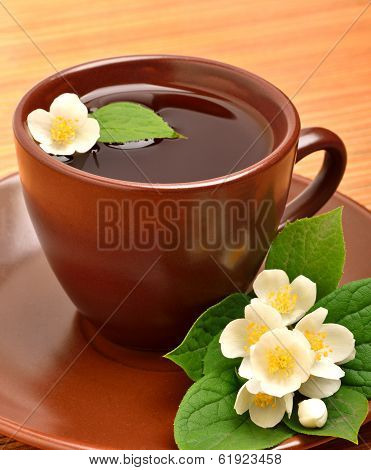 Tea Cup With Jasmine Flower On The Wood
