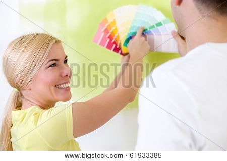 Happy couple choosing colors for painting house, concept of decoration