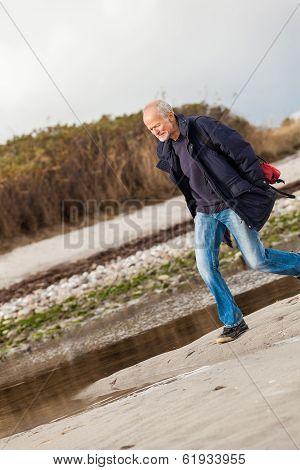 Elderly Energetic Man Running Along A Beach