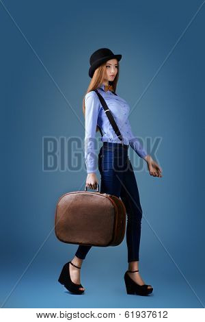 Elegant girl model in  bowler hat poses with the old suitcase. Refined style of old Europe. Full length.