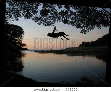 Silhouette Of Boy On Rope Swing