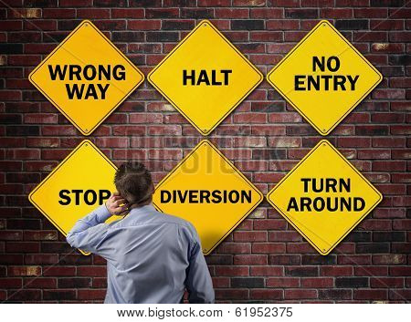 Businessman going the wrong way in front of a brick wall with stop, wrong way, halt, no entry, diversion and turn around road signs concept for blocked direction in business