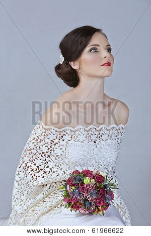 beautiful young bride with red lips wearing vintage lace dress and bright flowers on studio background