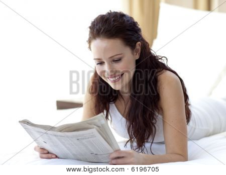 Brunette Woman In Bed Reading A Newspaper