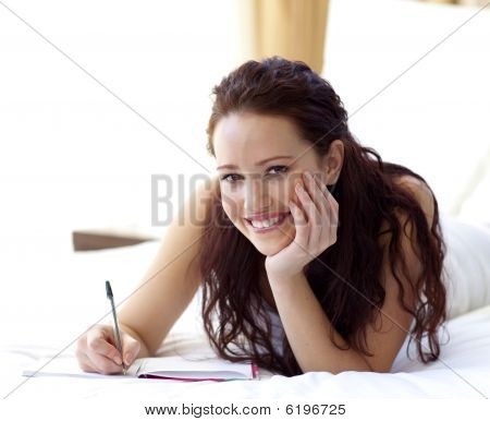 Beautiful Woman Writing Notes In Bed