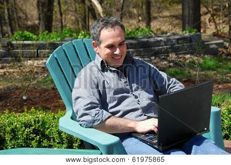Man working on a thinkpad outside