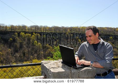 Smiling man working outdoors, wireless concept