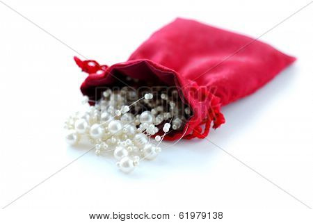 Pearls in red pouch on white background