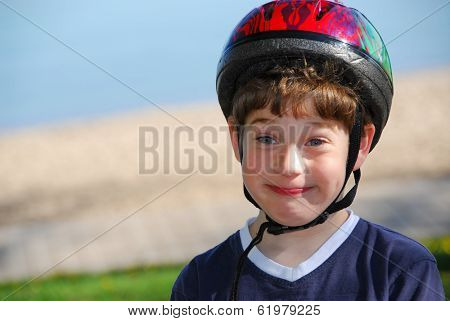 Portrait of a cute little boy in bicycle helmet making silly faces