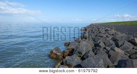 Dike with a stony shore along a lake in spring