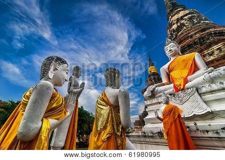Praying Buddhas at Wat Yai Chai Mongkhon temple under blue sky. Ayutthaya Thailand