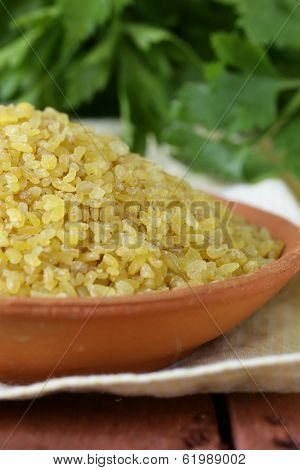 bulgur in a ceramic bowl on wooden table
