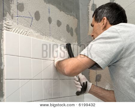 Man Tiling A Wall