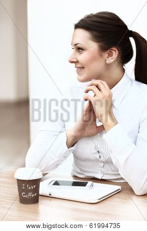 Happy young businesswoman using tablet computer in a cafe.