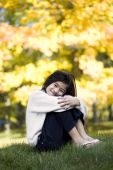 Little girl hugging knees sitting on lawn against bright autumn leaves in background pic.