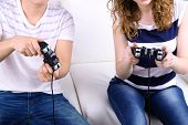 stock photo of indoor games  - Girl and boy playing video games at home - JPG