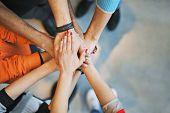 stock photo of stand up  - Multiethnic group of young people putting their hands on top of each other - JPG