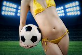 stock photo of string bikini  - Sexy woman wearing yellow bikini holding a soccer ball in field - JPG