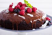 stock photo of tort  - Vegan chocolate cake with berries and coconut on top